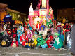 Masked people in front of a carnival float representing the Disney's Castle in Burano